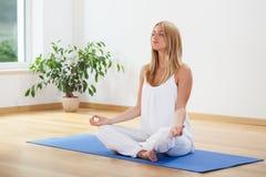 Yoga di pratica della donna a casa Fotografia Stock