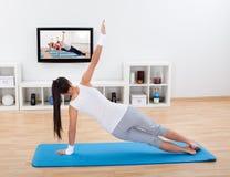 Yoga di pratica della donna a casa Immagini Stock