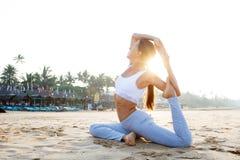 Yoga di pratica della donna caucasica alla spiaggia dell'oceano tropicale Immagini Stock Libere da Diritti