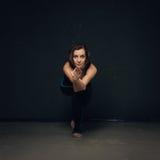 Yoga di pratica della donna contro una parete strutturata scura Fotografia Stock Libera da Diritti