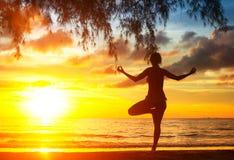 Yoga di pratica della donna della siluetta sulla spiaggia Fotografie Stock Libere da Diritti