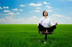 Yoga di pratica della donna di affari al prato Immagine Stock