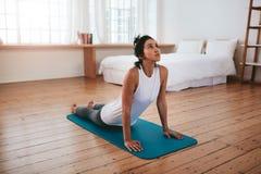 Yoga di pratica della donna di forma fisica a casa Fotografie Stock
