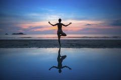 Yoga di pratica della donna durante il tramonto alla spiaggia Fotografia Stock
