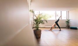 Yoga di pratica della donna di forma fisica all'interno Fotografia Stock Libera da Diritti