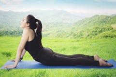 Yoga di pratica della donna graziosa nel prato Fotografie Stock