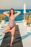 Yoga di pratica della donna incinta alla spiaggia Immagini Stock