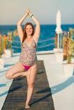 Yoga di pratica della donna incinta alla spiaggia Immagine Stock Libera da Diritti
