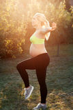 Yoga di pratica della donna incinta presto nella mattina Immagine Stock Libera da Diritti