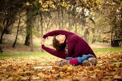 Yoga di pratica della donna nel parco di autunno Immagini Stock Libere da Diritti