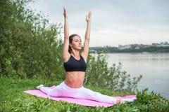 Yoga di pratica della donna nella posa della scimmia di hanumanasana della natura Immagini Stock