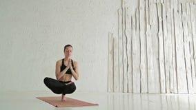 Yoga di pratica della donna - padangusthasana di padma di baddha di ardha - che equilibra sulle dita del piede