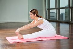 Yoga di pratica della donna in palestra Immagini Stock