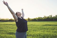 Yoga di pratica della donna di peso eccessivo sul prato fotografia stock
