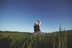Yoga di pratica della donna di peso eccessivo sul prato immagine stock
