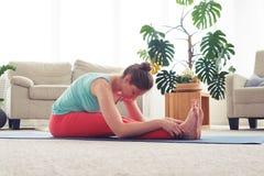 Yoga di pratica della donna rilassata nella posa di yoga del testa--ginocchio Immagini Stock Libere da Diritti
