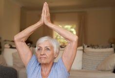Yoga di pratica della donna senior adatta da solo a casa Immagine Stock Libera da Diritti