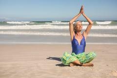 Yoga di pratica della donna senior mentre sedendosi contro il chiaro cielo Immagini Stock Libere da Diritti