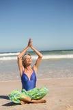 Yoga di pratica della donna senior mentre sedendosi contro il mare Immagine Stock Libera da Diritti