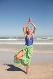Yoga di pratica della donna senior mentre stando contro il mare Fotografia Stock