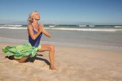 Yoga di pratica della donna senior sulla sabbia Fotografia Stock Libera da Diritti