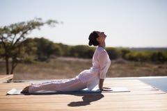 Yoga di pratica della donna sopra al poolside Fotografia Stock