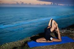 Yoga di pratica della donna su una roccia sopra il mare fotografia stock libera da diritti