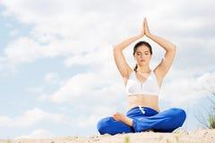 Yoga di pratica della donna su una spiaggia Immagini Stock Libere da Diritti
