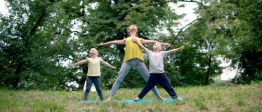 Yoga di pratica della famiglia per felicità in natura fotografie stock
