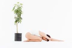 Yoga di pratica della giovane donna afroamericana rilassata sul pavimento Immagini Stock