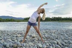 Yoga di pratica della giovane donna al fiume della montagna Fotografia Stock