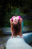 Yoga di pratica della giovane donna all'aperto Fotografia Stock