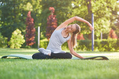 Yoga di pratica della giovane donna all'aperto al parco Fotografia Stock