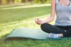 Yoga di pratica della giovane donna all'aperto al parco Immagine Stock