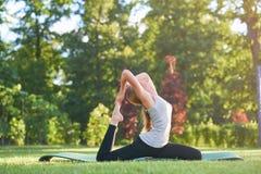 Yoga di pratica della giovane donna all'aperto al parco Immagini Stock