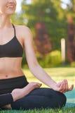 Yoga di pratica della giovane donna all'aperto al parco Fotografie Stock