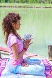 Yoga di pratica della giovane donna all'aperto dal concetto sano di stile di vita del fiore della magnolia della tenuta del lago immagine stock libera da diritti