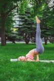 Yoga di pratica della giovane donna attraente all'aperto Fotografia Stock