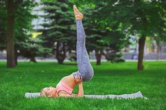 Yoga di pratica della giovane donna attraente all'aperto Immagini Stock Libere da Diritti