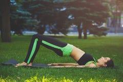 Yoga di pratica della giovane donna attraente all'aperto Immagine Stock Libera da Diritti