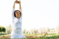 Yoga di pratica della giovane donna attraente all'aperto Fotografie Stock Libere da Diritti