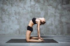 Yoga di pratica della giovane donna attraente, allungante nell'esercizio di Ustrasana, nella posa del cammello, nell'interno dell Immagini Stock