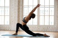 Yoga di pratica della giovane donna attraente degli Yogi, facente anjaneyasana immagini stock