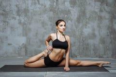 Yoga di pratica della giovane donna attraente, risolvendo, abiti sportivi neri d'uso, stile urbano fresco, fondo grigio dello stu Fotografie Stock Libere da Diritti
