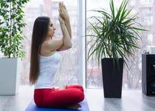 Yoga di pratica della giovane donna attraente, sedentesi nell'esercizio di Ardha Padmasana, mezza posa di Lotus, risolvendo, magl fotografie stock