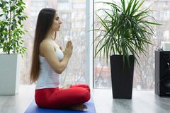 Yoga di pratica della giovane donna attraente, sedentesi nell'esercizio di Ardha Padmasana, mezza posa di Lotus, risolvendo, magl immagine stock libera da diritti