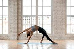 Yoga di pratica della giovane donna attraente sportiva, facente cosa selvaggia immagini stock