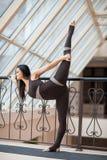 Yoga di pratica della giovane donna attraente, stante nell'esercizio di Natarajasana, signore della posa di ballo, risolvendo, ab Immagini Stock