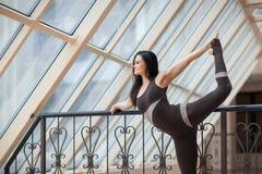 Yoga di pratica della giovane donna attraente, stante nell'esercizio di Natarajasana, signore della posa di ballo, risolvendo, ab Fotografie Stock Libere da Diritti