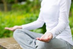 Yoga di pratica della giovane donna attraente in un parco Immagini Stock